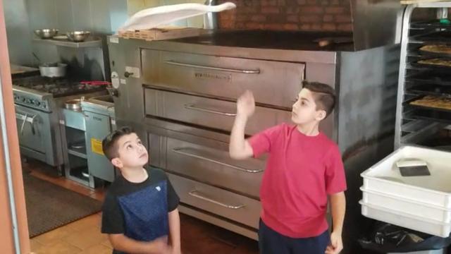 Jongens tonen talent voor pizza's gooien in Amerikaans restaurant