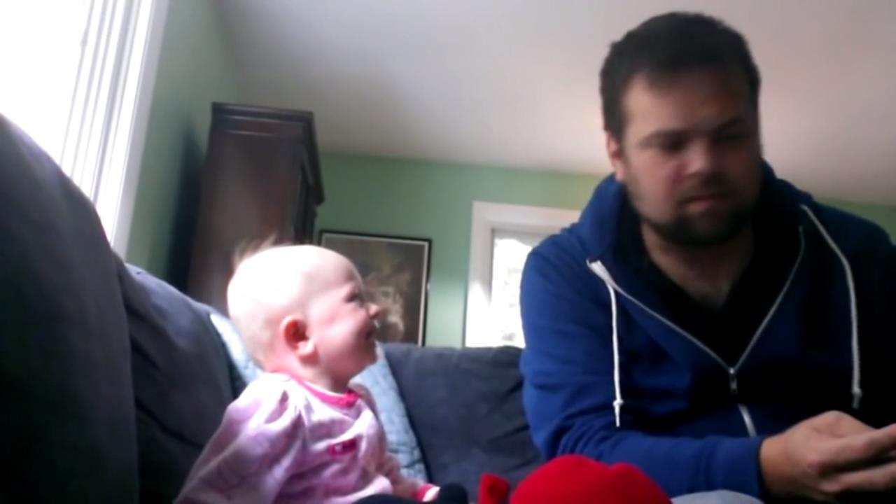 Baby ligt dubbel om voorlezende vader