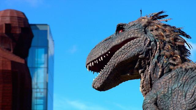 T.rex oog in oog met mega mensfiguur