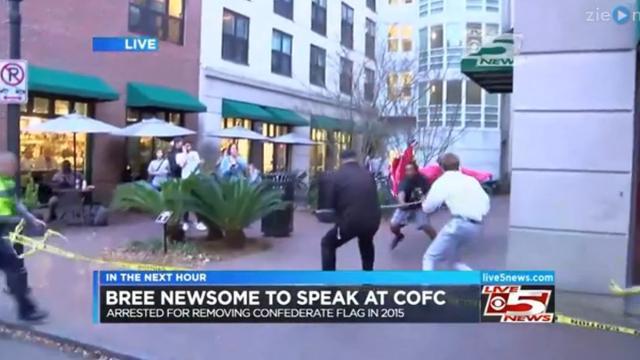 Demonstrant grijpt vlag van de Confederatie tijdens live televisie
