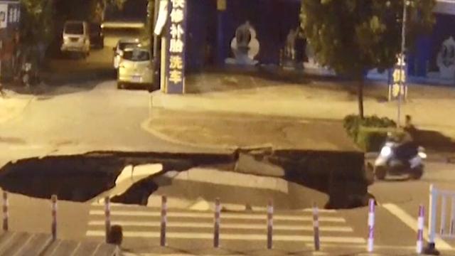 Onoplettende scooterrijder China rijdt net ontstaan zinkgat in