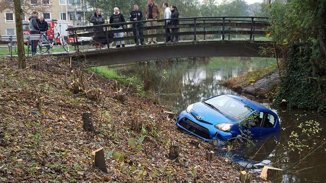 Auto door bosjes en over fiets- en voetpad het water in