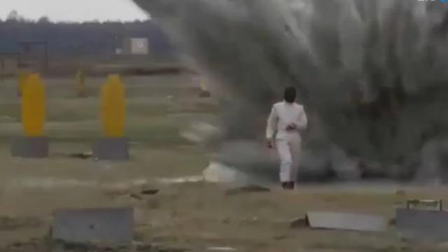Vrouw in speciaal pak loopt dwars door explosies
