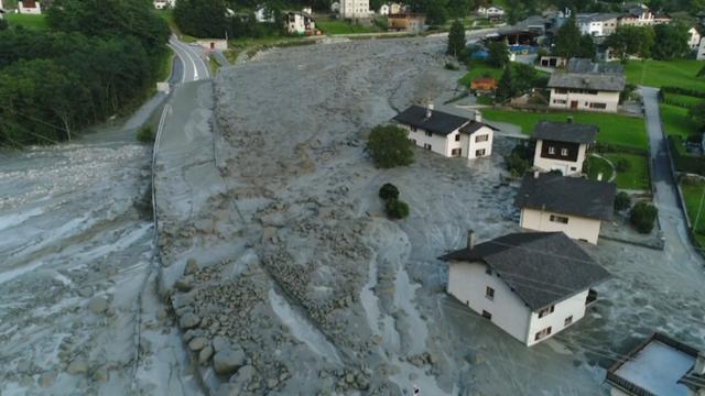 Modderstroom bedekt stadje in Zwitsers bergdal Val Bregaglia