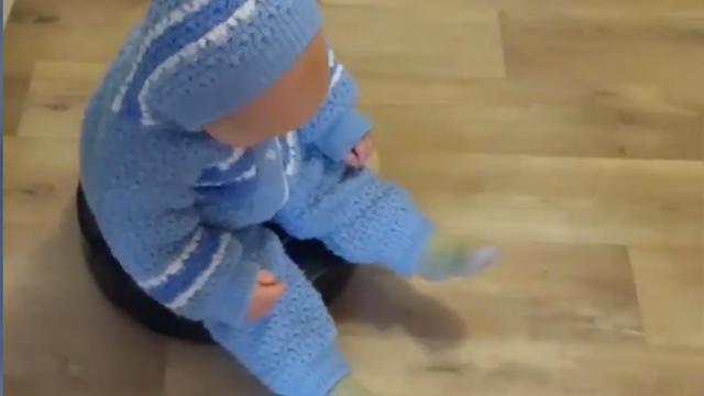Baby geniet van ritje bovenop robotstofzuiger