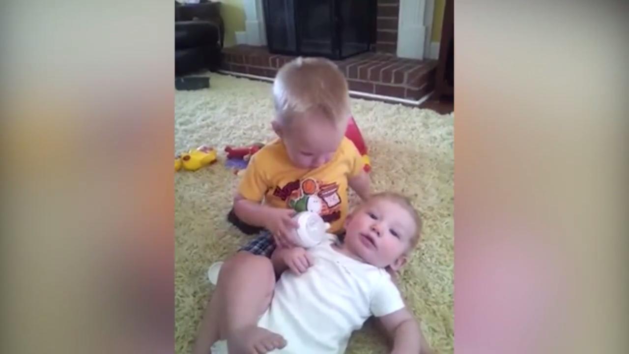 Peuter geeft zijn broertje de fles