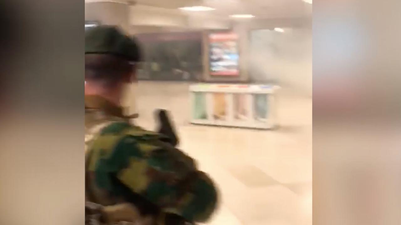 Militairen lopen door rook in leeg station Brussel na explosie