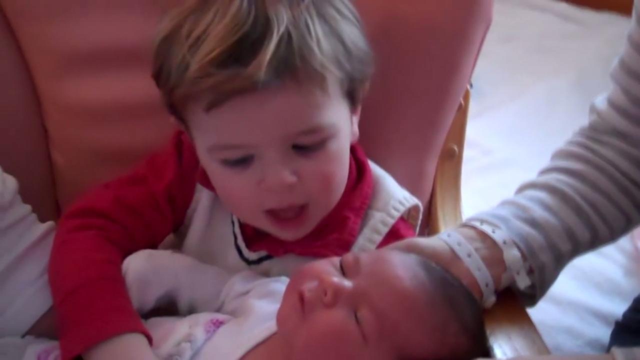 Jongetje voert gesprek met pasgeboren zusje
