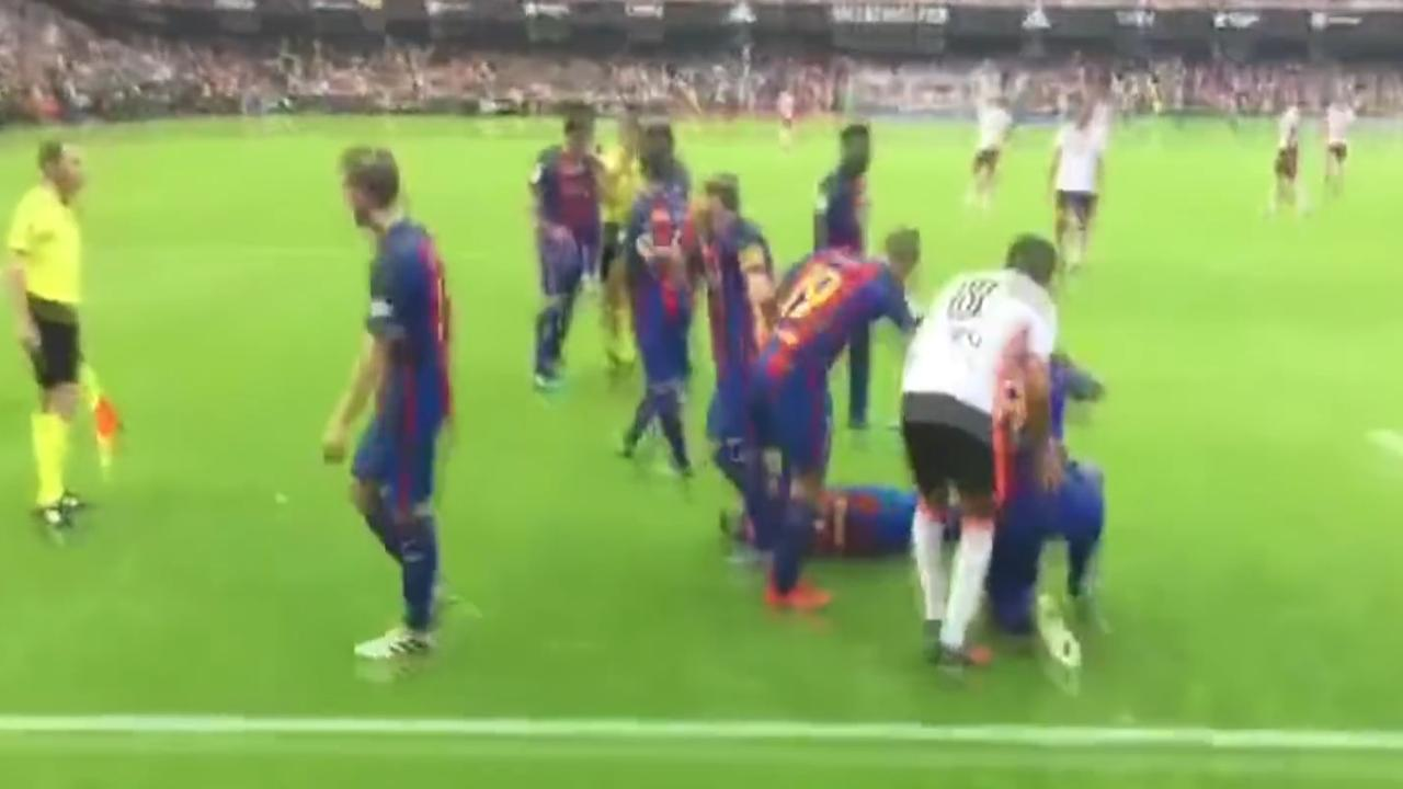 Valencia-supporter raakt juichende Barcelona-spelers met flesje water