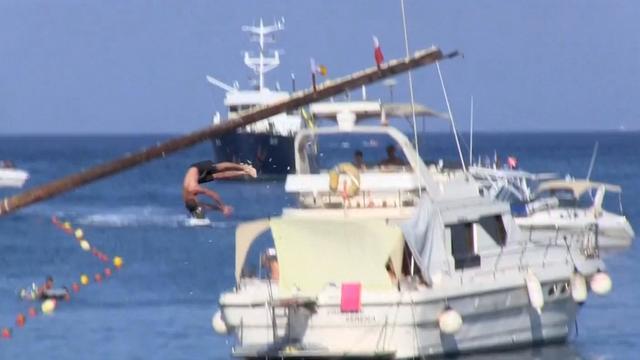 Festivalgangers op Malta doen mee aan wedstrijd paal klimmen