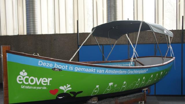 Sloep van grachtenafval te water aan de Herengracht