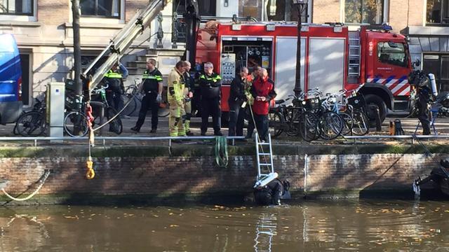 Auto met twee inzittenden rijdt Herengracht in