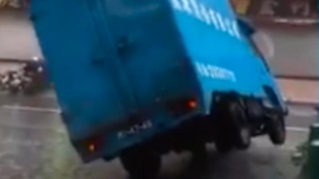 Kantelende vrachtauto en op hol geslagen hijskraan door tyfoon Hato