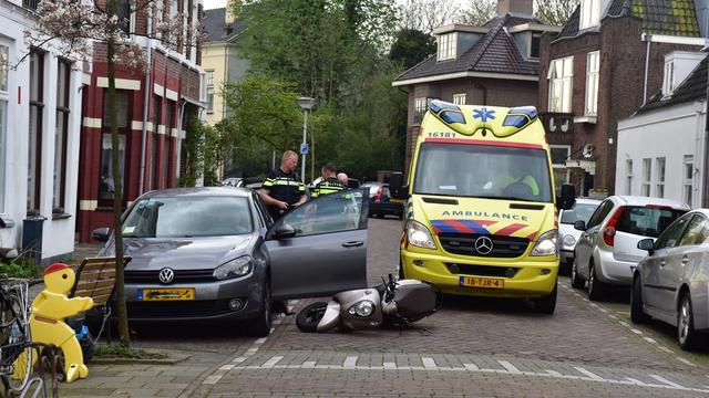 Scooterrijdster knalt tegen autoportier en belandt in ziekenhuis