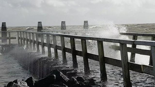 Harde wind blaast water op Afsluitdijk