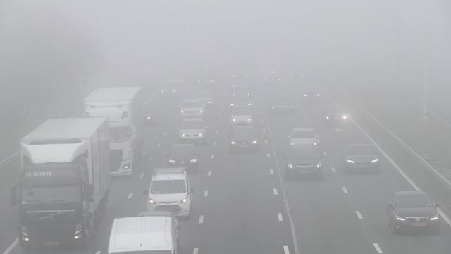 Automobilisten rijden in dichte mist op snelweg bij Schiphol
