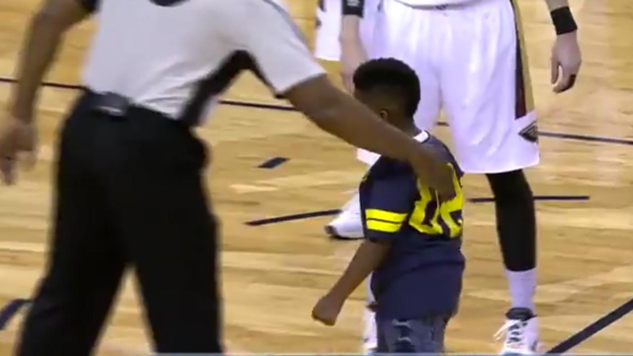 Kind knuffelt basketballer Anthony tijdens wedstrijd