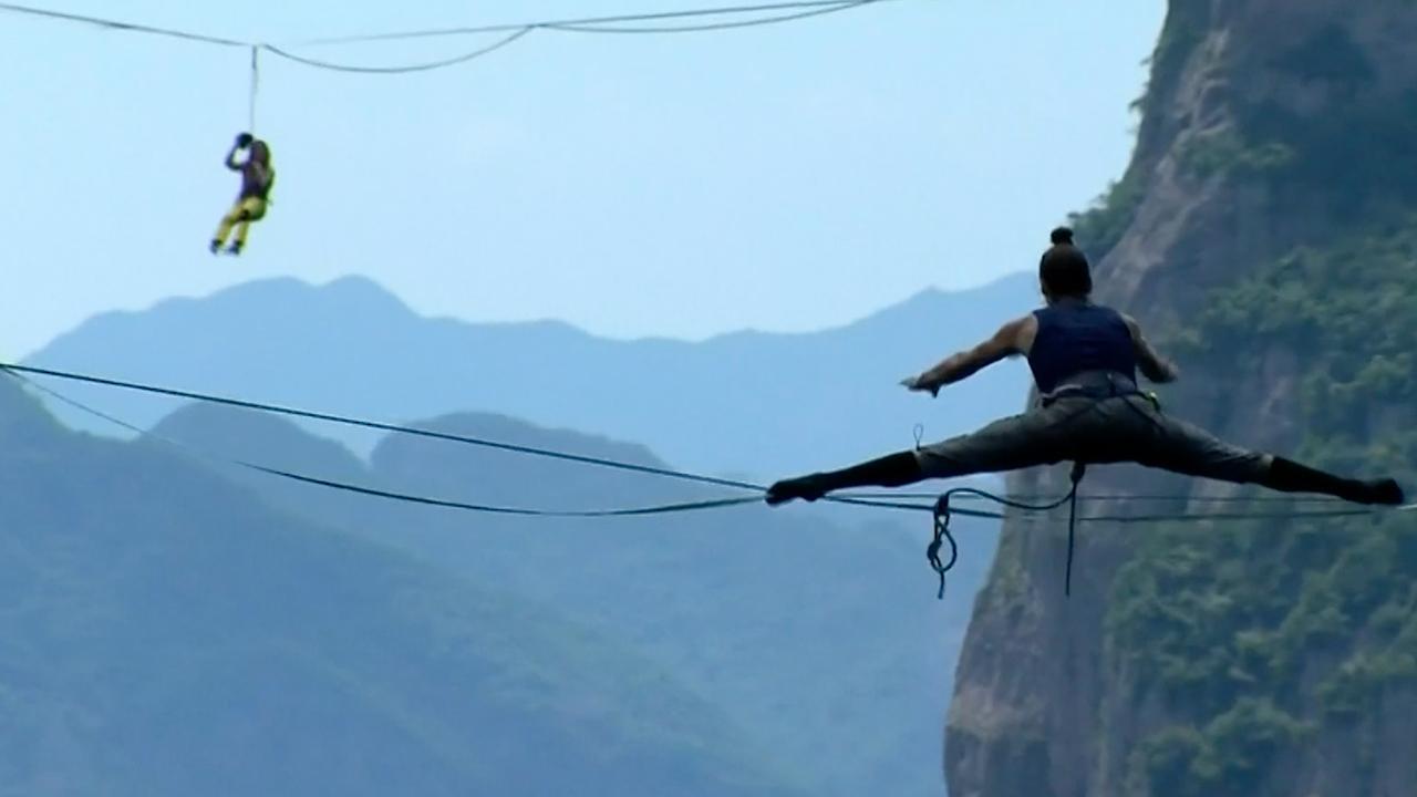 Waaghalzen nemen het in China tegen elkaar op tijdens slacklinewedstrijd