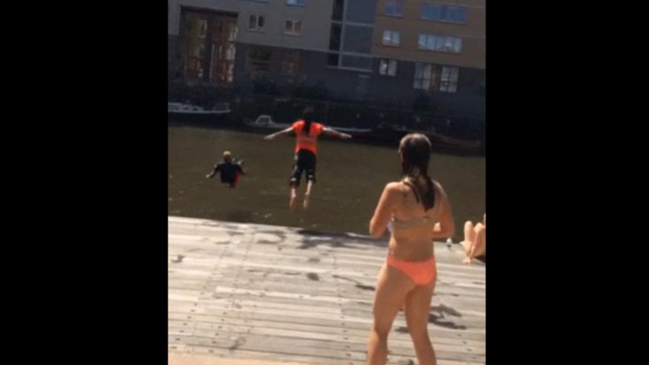 Amsterdamse vuilnismannen springen in water Entrepotdok