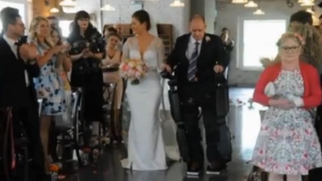 Verlamde Britse man loopt dochter naar altaar in robotpak