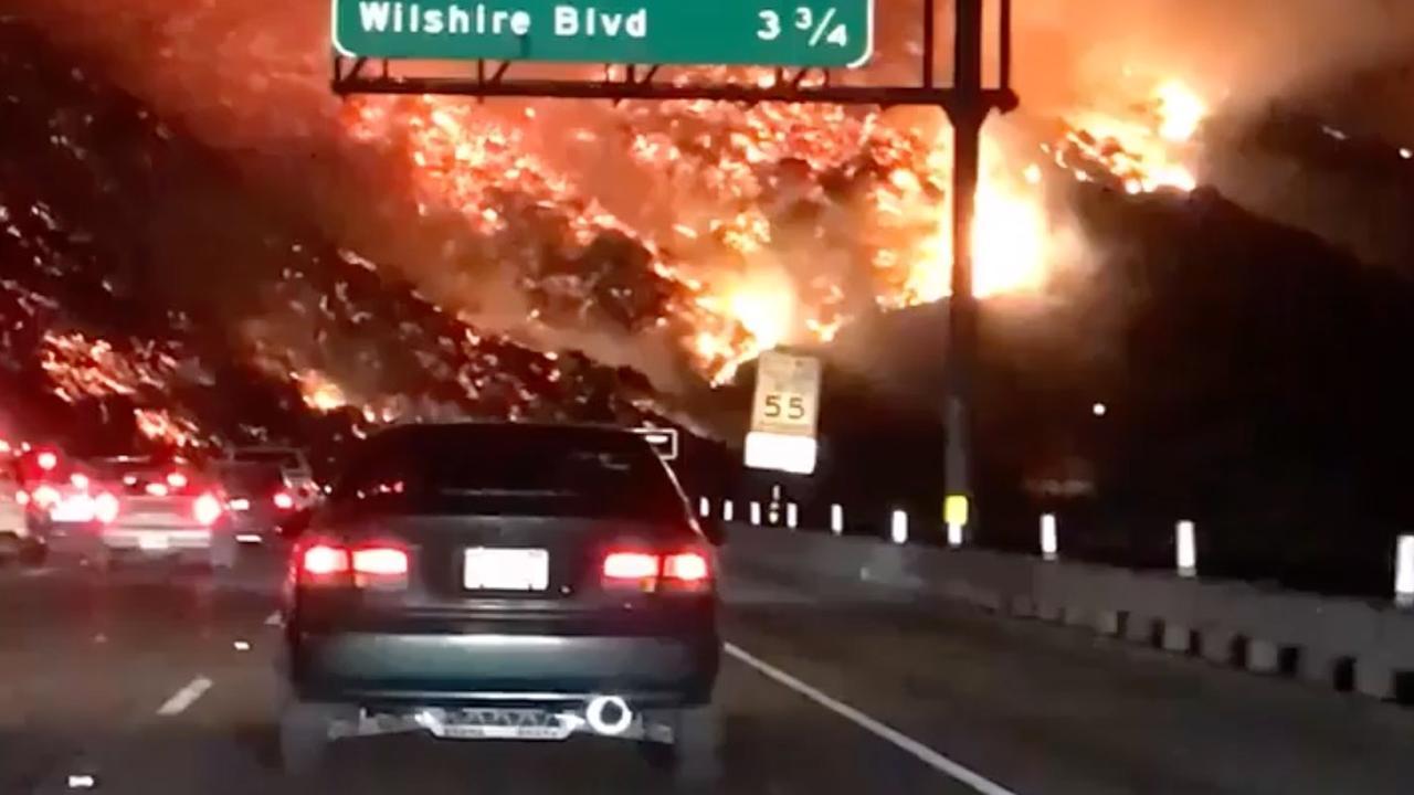 Vlammen grijpen om zich heen naast grote snelweg Californië