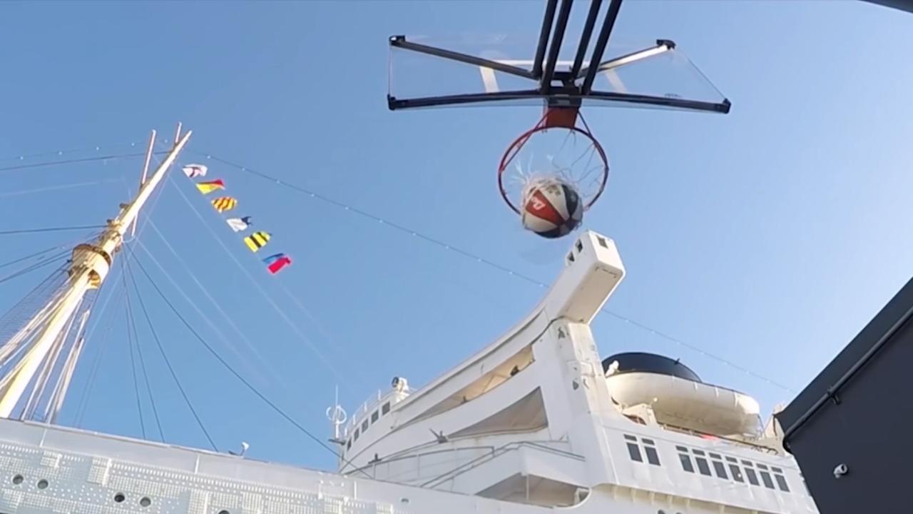 Harlem Globetrotters schieten bal door basket vanaf cruiseschip