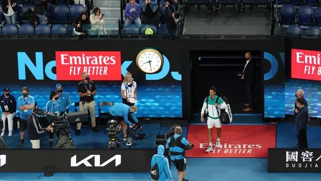Met publiek op de tribune betreedt Novak Djokovic de Rod Laver Arena.