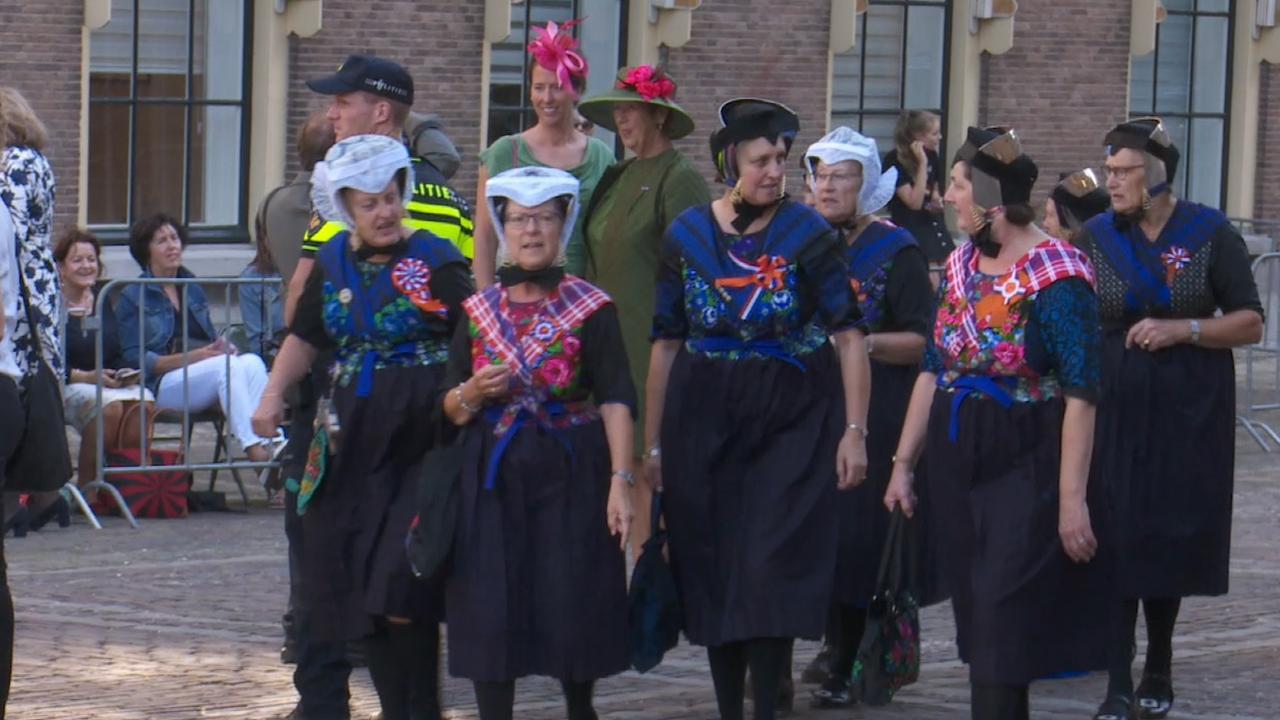 Dames in klederdracht arriveren op Binnenhof