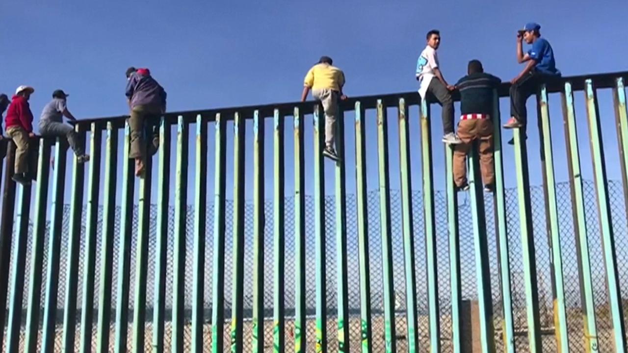 Eerste migranten bij Amerikaanse grens klimmen in hekken