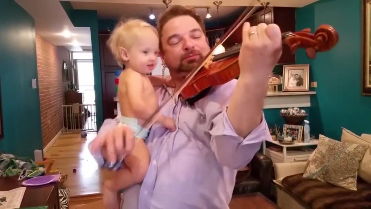Meisje swingt mee op arm vader tijdens viool spelen