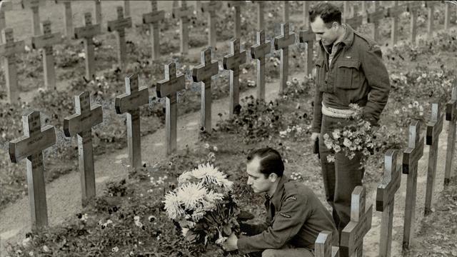 1944: Canadese soldaten leggen bloemen op een begraafplaats voor landgenoten die eerder omkwamen bij luchtgevechten boven Nederland.