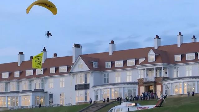 Paraglider vliegt met spandoek over hoofd Trump
