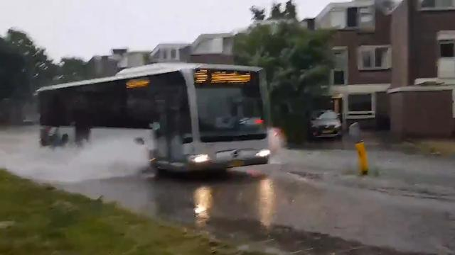 Bus rijdt door hoogstaand water in Vlaardingen