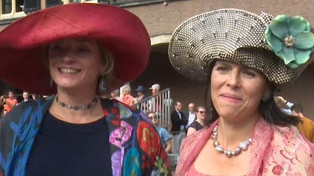 Vrouwen met feestelijke hoeden komen aan op Binnenhof