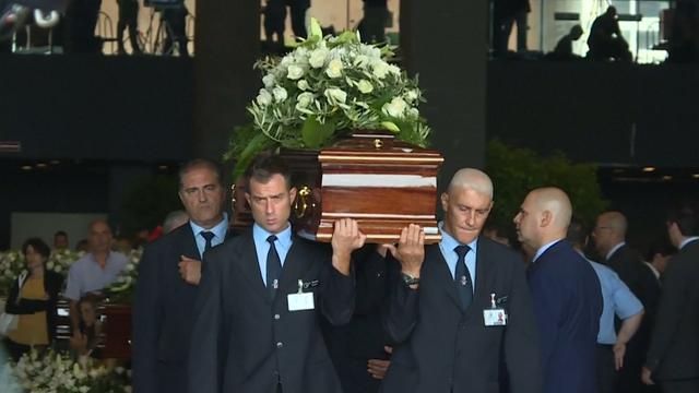 Kistdragers lopen met doodskisten slachtoffers Genua bij uitvaart