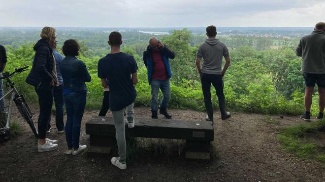 Vanaf een heuvel kijken mensen hoe hun huis mogelijk wordt overspoeld.