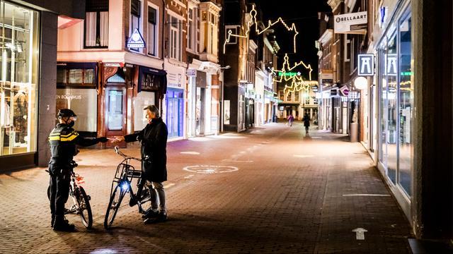 Een passant in Haarlem laat aan de politie een verklaring zien waarom hij buiten moet zijn.