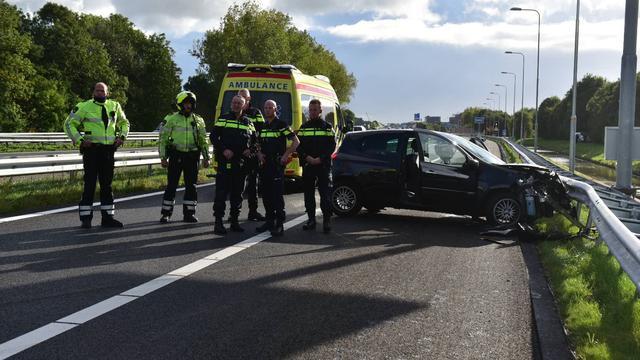 Auto in vangrail na botsing tegen verkeersbord