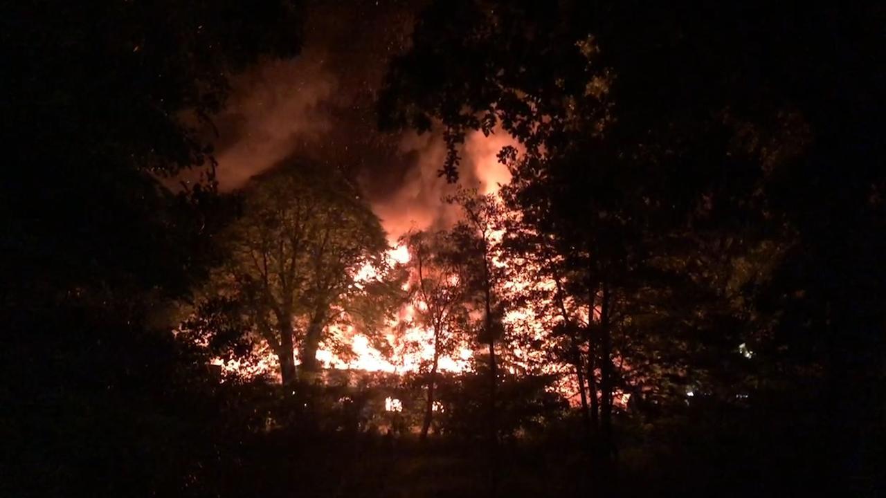Vlammen slaan uit dak bij brand in school Ede