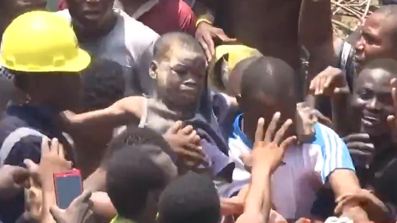 Kind wordt afgevoerd na instorten school Nigeria