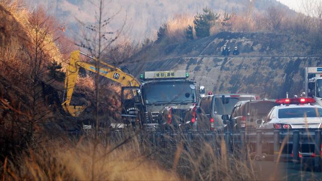 Graafmachines maken een snelweg schoon. Die raakte geblokkeerd door een aardverschuiving.