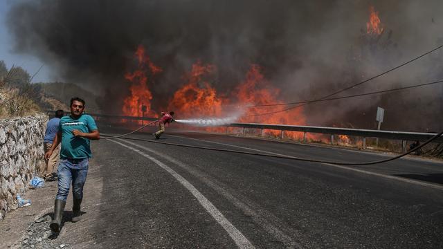 Brandweerlieden strijden tegen de vlammen in de heuvels rondom de populaire Turkse badplaats Marmaris.