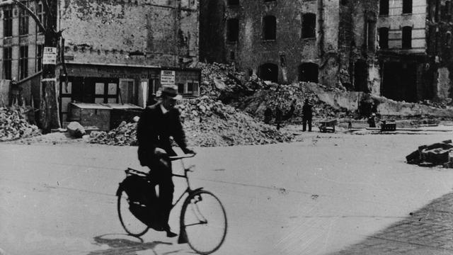 1941: Een fietser rijdt tussen de ruïnes in Rotterdam.