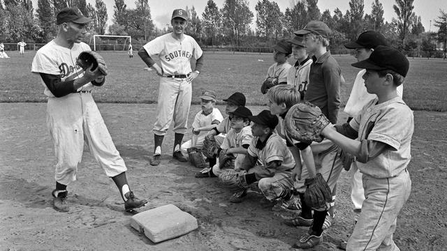 Han Urbanus geeft een training aan jonge honkballers.