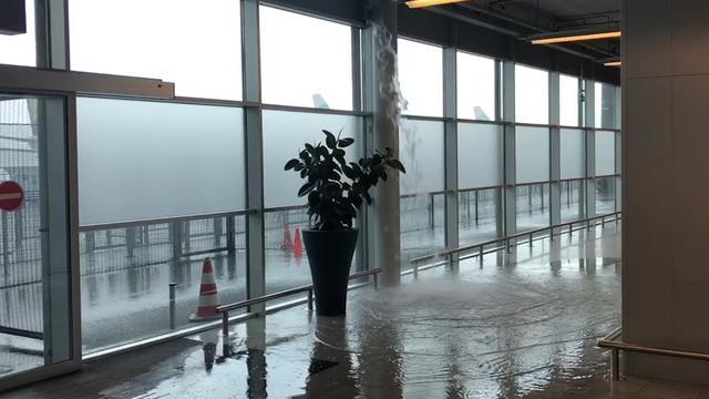 Water stroomt aankomsthal Eindhoven Airport binnen na zware buien