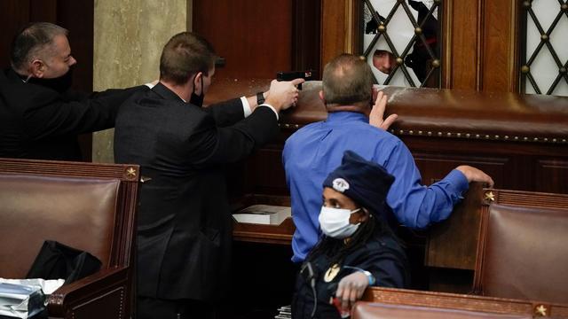 Veiligheidsagenten met getrokken wapens in het Huis van Afgevaardigden.