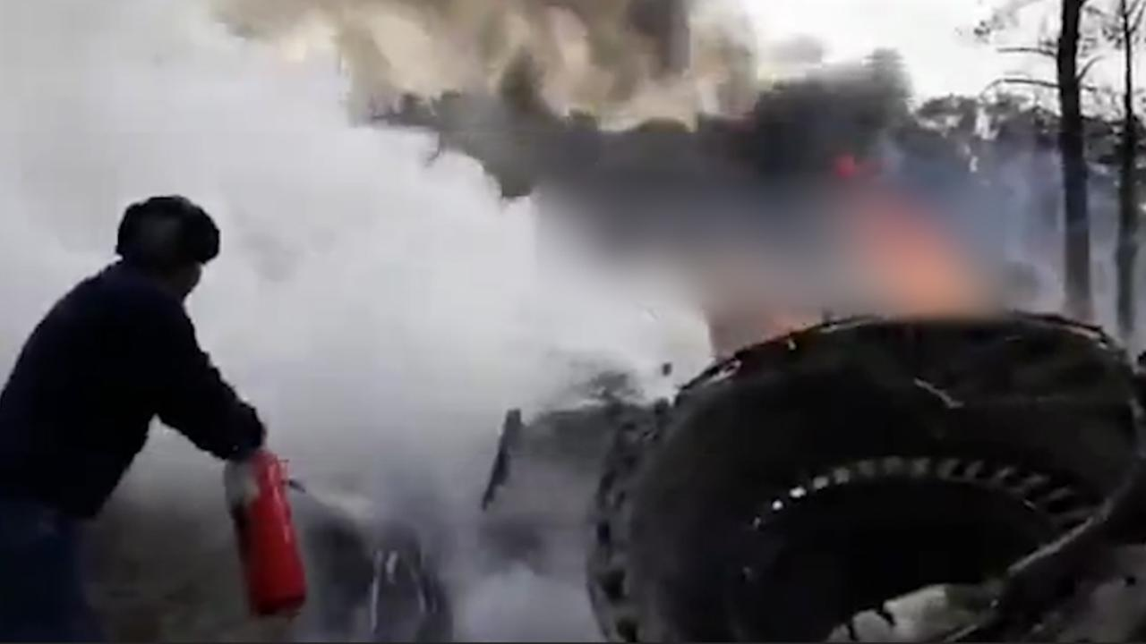 Omstanders blussen wrak na vliegtuigcrash Iran