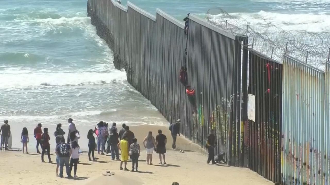 Migranten klimmen over hoge grensmuur tussen Mexico en VS