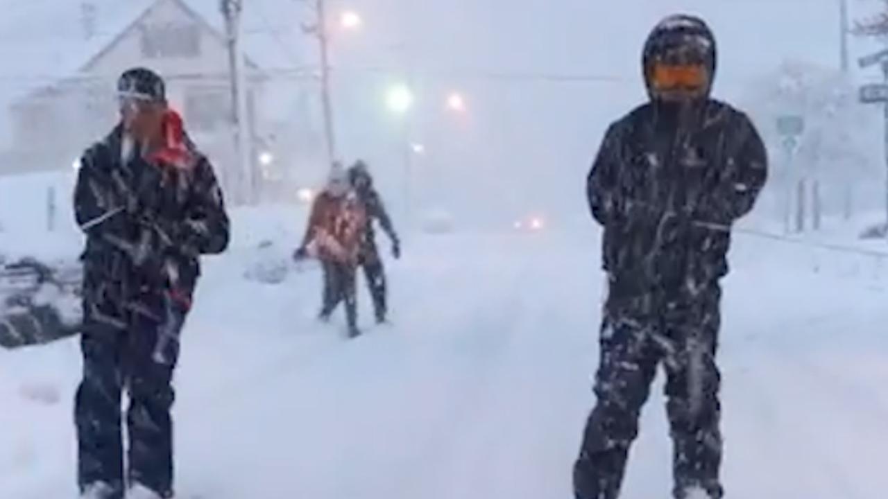 Mannen skiën door besneeuwde straten van New Jersey