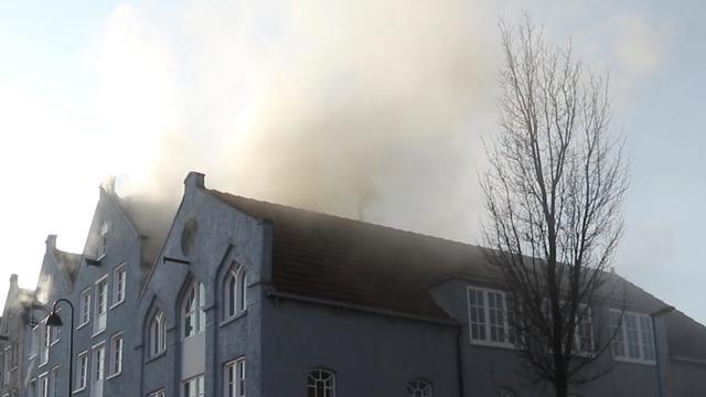 Donkere rookwolken komen uit oud pand in Maassluis